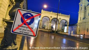 Перечеркнутый уличный знак в Мюнхене с требованием носить маску