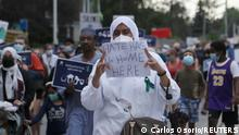 A woman holds a sign as people march the 7km from a crime scene to a mosque in memory of a Muslim family that was killed in what police call a hate-motivated attack in London, Ontario, Canada June 11, 2021. REUTERS/Carlos Osorio