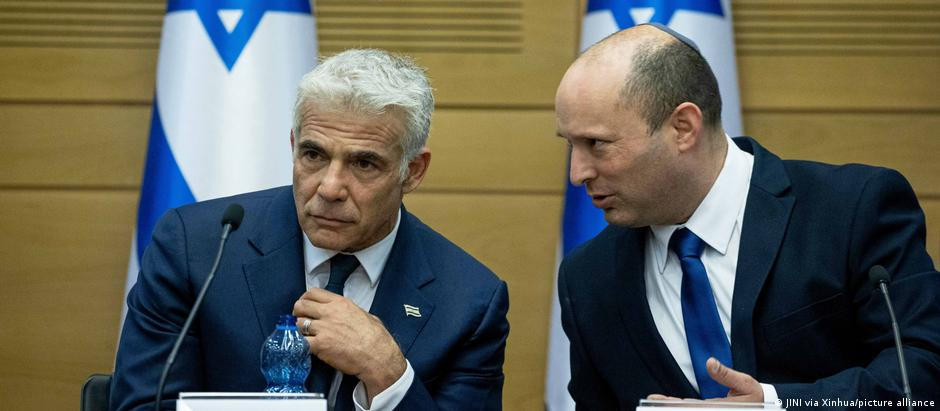 Israel's new Prime Minister Naftali Bennett (right) and Yair Lapid, Israel's alternate prime minister and foreign minister, discuss at a cabinet meeting
