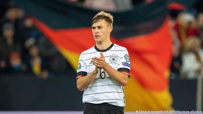 Joshua Kimmich standing in front of a Germany flag
