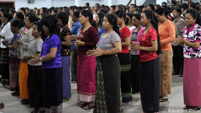 Some of Ziona Chana's wives and family praying at a church ceremony in India
