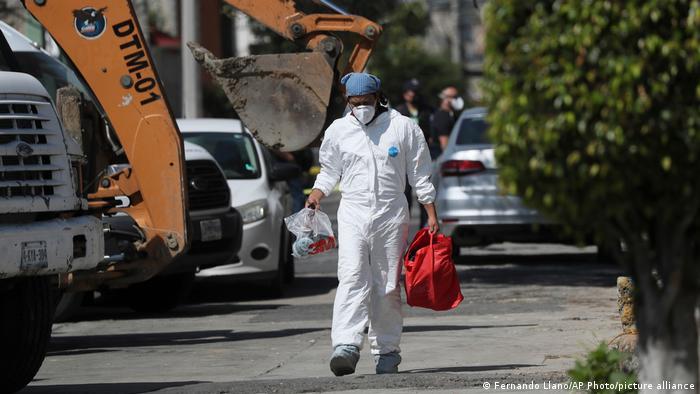 Un investigador forense lleva equipo fuera de la casa donde la policía encontró huesos bajo el suelo en el municipio de Atizapán del Estado de México.