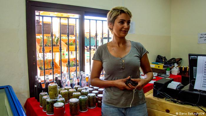 Female farmer Mariam stands close to the jars that she produces at home and goes to sell to the shop of Baalbek Community Farm