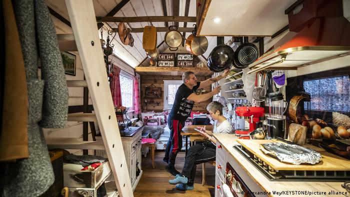 Two people inside of a tiny house where kitchen utensils hang from the wooden ceiling
