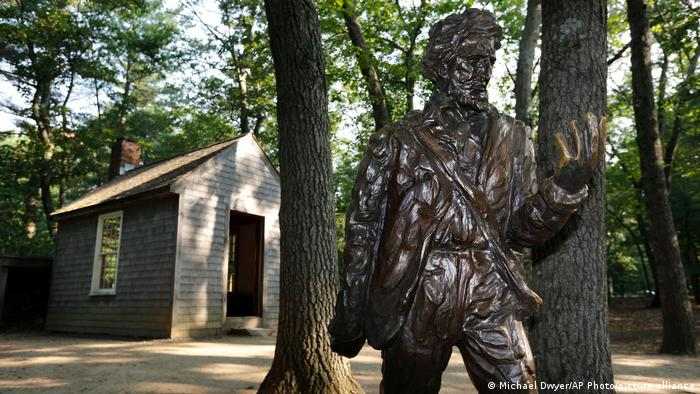 A statue of philosopher Henry David Thoreau in front of a re-creation of his cabin at Walden Pond