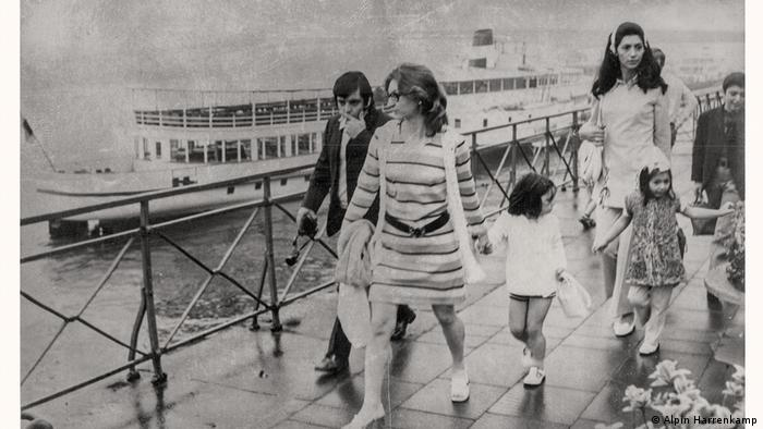 Several adults and children walking along the Rhine River, boat in the background