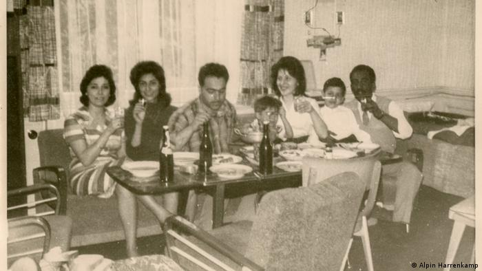 Six people sitting at a table, eating and drinking
