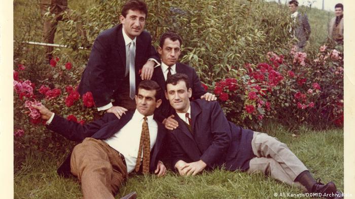 Four men pose in front of rose bushes