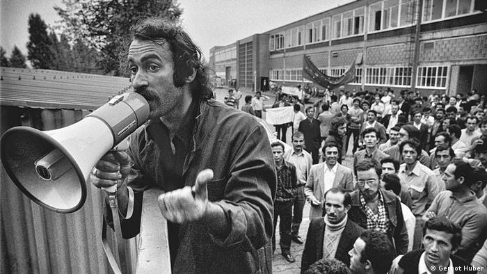 Man speaking into a megaphone, crown behind him