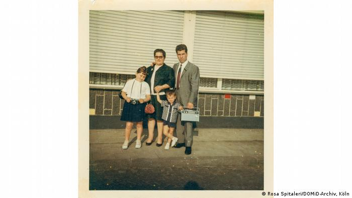 A family with two kids poses with a transistor radio