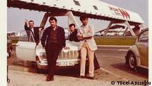 """Yücel Aşçıoğlu (links) mit Freunden auf dem Weg nach Paris Nahe Paris, 1971 """"Es war der Osterurlaub. Wir fuhren mit Zekis Auto vom Wohnheim aus nach Paris. Unterwegs hielten wir an einem Rastplatz in der Nähe von Paris, wo dieses Foto aufgenommen ist. Wir haben es von jemandem machen lassen, damit wir alle auf dem Foto sein konnten. Der Fotoapparat gehörte aber mir. Wir wollten unbedingt den Eiffelturm sehen."""" (Yücel Aşçıoğlu) © Yücel Aşçıoğlu"""