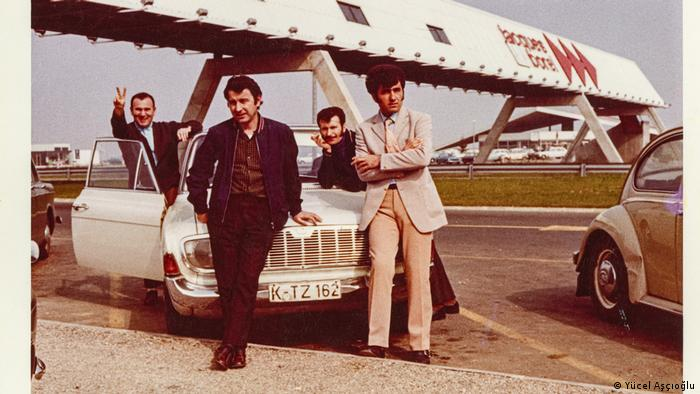 Four young men stand around a white car
