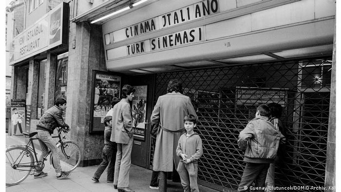 Foto da mostra sobre trabalhadores convidados exibe fachada de um cinema fechado, com pessoas a sua frente