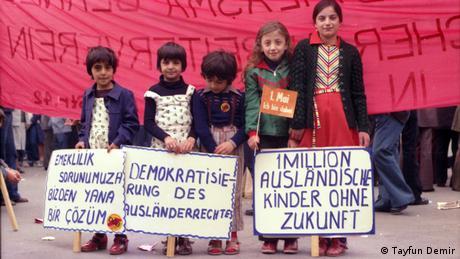Fünf Kinder stehen nebeneinander und halten Plakate während einer Demonstration hoch. Darauf zu lesen: 1 Million ausländische Kinder ohne Zukunft.