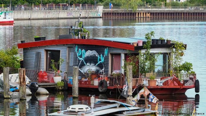 A colorful house boat with plants on its deck