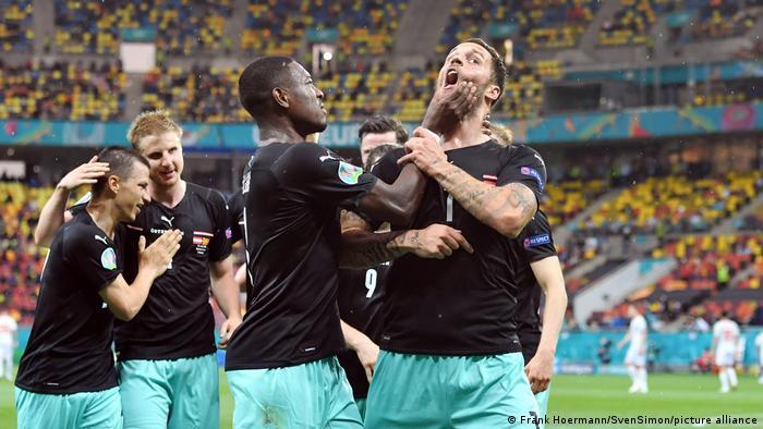 Austria captain David Alaba reprimands Marko Arnautovic, far right, for his impassioned goal celebration against North Macedonia.