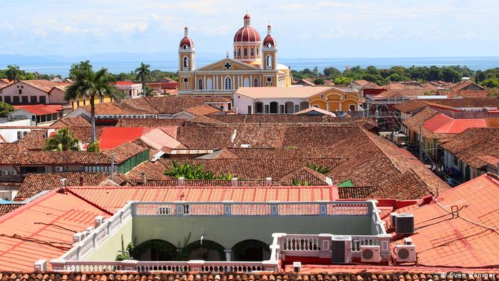A series of red rooftops and Granada Cathedral in the background.