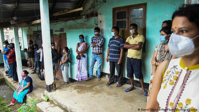People wait to get a vaccine against COVID-19 at a vaccination centre in Guwahati, India