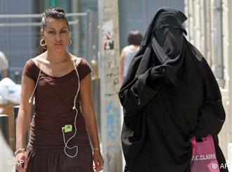 Two women on a street in Paris, one wearing the burqa, one not.