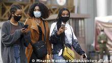 Drei Frauen mit Maske laufen über eine Straße und tippen auf ihren Smartphones