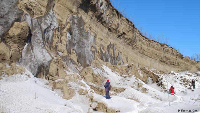Foto mostra o permafost. Há uma parede de terra e um pouco de neve no chão. Três pessoas observam.