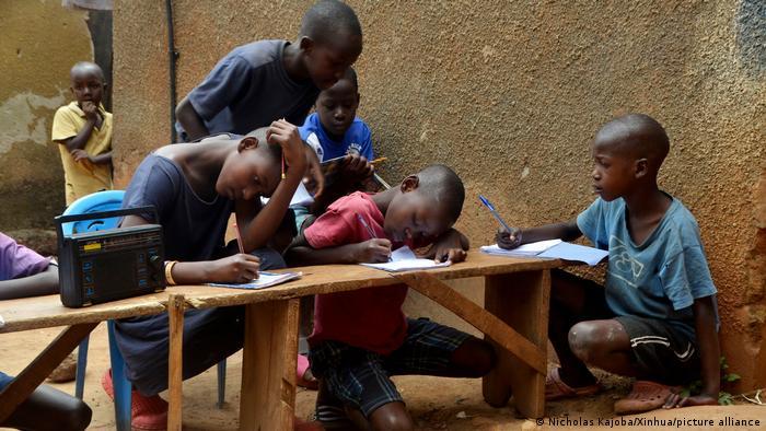 Kinder sitzen neben einem Radio und schreiben in Hefte