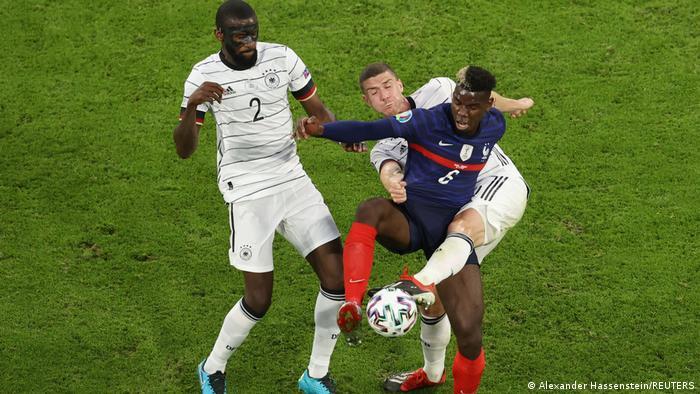آبیپوشان فرانسه بازی را محتاطانه آغاز کردند، اما آرامآرام بر فشار خود بر آلمان افزودند و در عرض یک ربع نخست بازی دو بار خطرآفرین شدند. تصویری از تلاش بازیکان آلمان برای مهار پوگبا، هافبک پرتوان تیم ملی فرانسه.