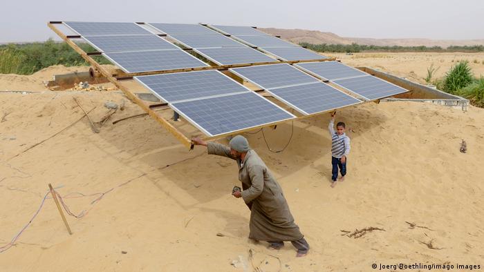 Ein Mann und ein Kind vor einer Solaranlage