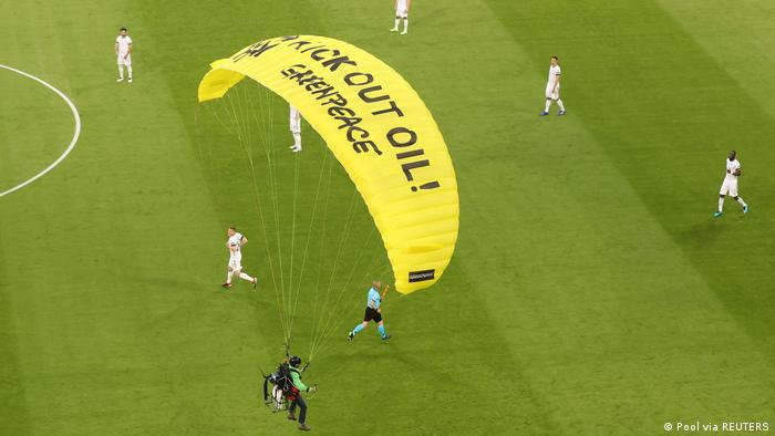 A Greenpeace protestor glides on to the pitch before the match.