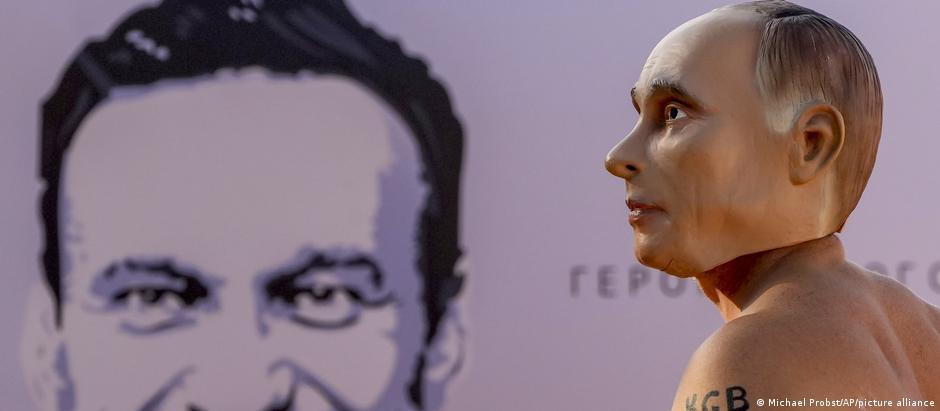 Чоловік у масці Володимира Путіна на тлі портрету Олексія Навального