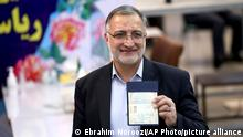 Former lawmaker Ali Reza Zakani shows an identification document to media while registering his candidacy for the upcoming presidential elections at the Interior Ministry in Tehran, Iran, Saturday, May 15, 2021. Iran named seven candidates Tuesday, May 15, for its June 18 presidential election, approving the candidacy of Zakani and hard-line cleric Ebrahim Raisi, while barring former parliament speaker Ali Larijani allied to the country's current president. (AP Photo/Ebrahim Noroozi)