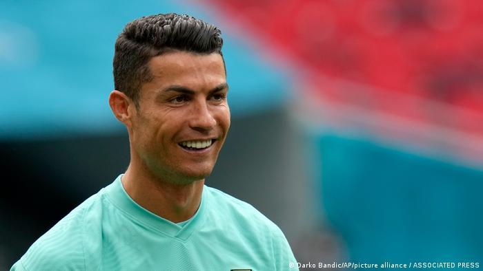 Foto de Cristiano Ronaldo. Ele sorri e usa camiseta azul claro. O fundo está desfocado.