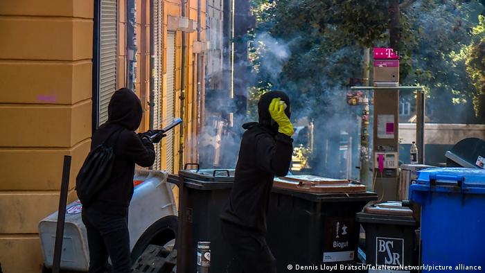 Two hooded individuals stand behind a makeshift barricade of trash containers, one about to throw a stone and the other holding what appears to be an air rifle, taking aim at police.