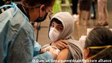 Ein Schüler schaut seine Mutter an, während er in einer schulischen Corona-Impfklinik für Schüler ab 12 Jahren geimpft wird. Schulbezirke von Kalifornien bis Michigan bieten kostenlose Eintrittskarten für den Abschlussball an und entsenden mobile Impfteams in die Schulen, um Schüler ab 12 Jahren zu impfen, damit alle im Herbst in die Klassenzimmer zurückkehren können. +++ dpa-Bildfunk +++