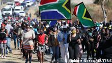 Community members hold flags during a march to protest against crime and undocumented immigrants in Soweto, South Africa, June 16, 2021. REUTERS/Siphiwe Sibeko