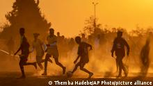 Soccer players play a friendly match on a dusty soccer field in Soweto, South Africa, Wednesday, June 16, 2021. (AP Photo/Themba Hadebe)