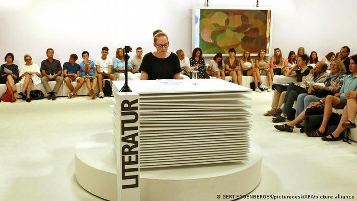 A person reading at a table made to look like pages of a manuscript, surrounded by an audience. In front of the table, there's a pillar with the word 'Literatur'.
