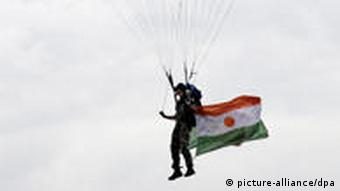 A man with a parachute in the colors of the French flag floats down with a flag from Niger attached to his boot