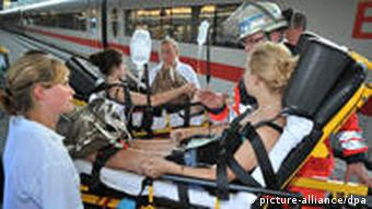 A girl is taken off a train on a stretcher