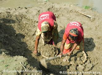 Two women gather up mud and dirt