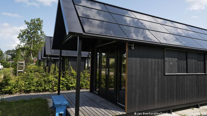 A row of tiny houses with solar panels on their roofs