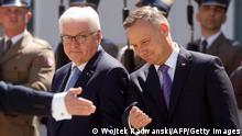 Polish President Andrzej Duda (R) gestures next to German President Frank-Walter Steinmeier (C) during a welcoming ceremony at the presidential palace in Warsaw, Poland, on June 17, 2021. - The German President has travelled for a one-day visit to Warsaw on the occasion of the 30th anniversary of the German-Polish neighborhood treaty. (Photo by Wojtek Radwanski / AFP) (Photo by WOJTEK RADWANSKI/AFP via Getty Images)