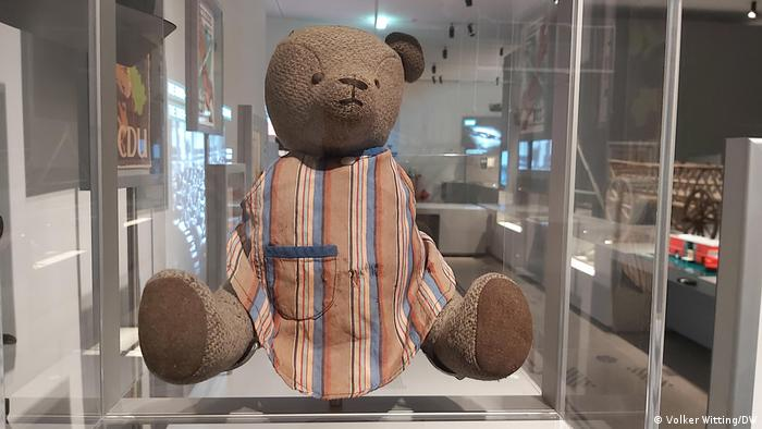 teddy bear with only one ear and no arms sitting in a glass case