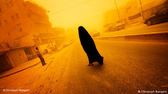 A photograph by Christoph Bangert showing a covered woman walking across a street in Iraq