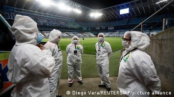 Люди в защитных костюмах на стадионе в Порту-Алегри, Бразилия