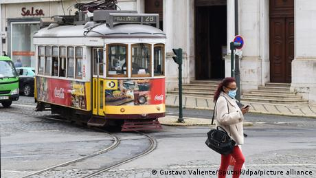 A woman wearing a protective face mask crosses the street next to a trolley car at Luis De Camoes Square, in Lisbon, Portugal