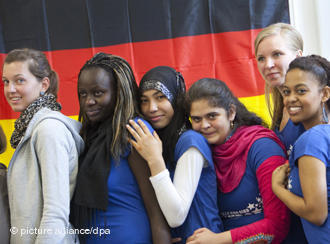 Young migrants in front of a German flag.