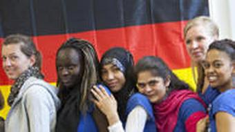 Teenagers of various backgrounds in front of German flag