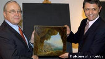 US ambassador William Timken, left, officially hands over the stolen paintings to Pirmasens mayor Bernhard Matheis in February, 2010