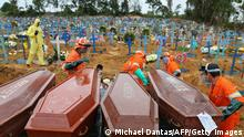 TOPSHOT - Coffins are unloaded to be buried in a mass grave at the Nossa Senhora cemetery in Manaus, Amazon state, Brazil on May 6, 2020. (Photo by MICHAEL DANTAS / AFP) (Photo by MICHAEL DANTAS/AFP via Getty Images)
